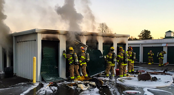 Firefighters fighting fire at storage facility.